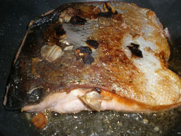 filete de salmón con ajos friendose